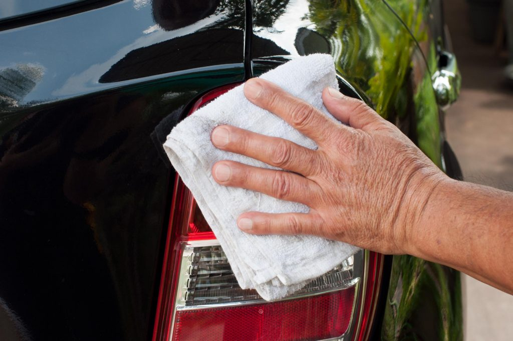 old person cleaning the car