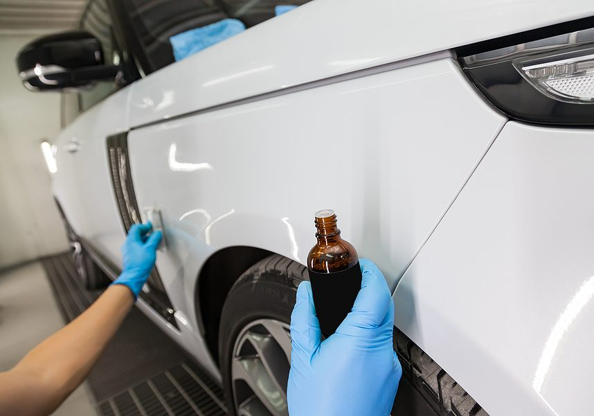 process of applying a nano-ceramic coating on the white car's fender by a male worker with a sponge and a bottle of chemical composition in the hand to protect the paint in detailing workshop.